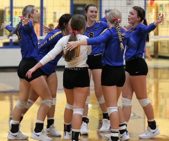 girls volleyball team celebrates